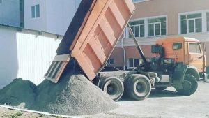 КАМАЗ разгружает песок